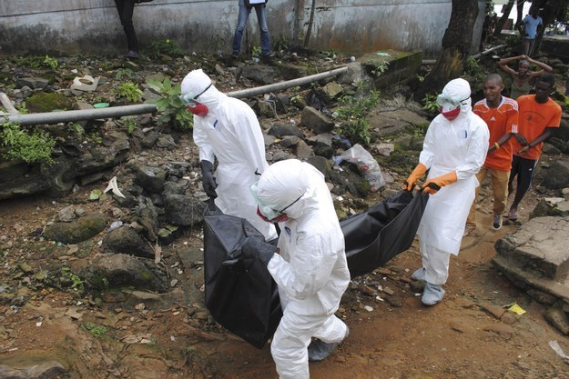 Health workers remove the body of a man whom local residents said died of Ebola in Monrovia, Liberia, in September (Reuters).