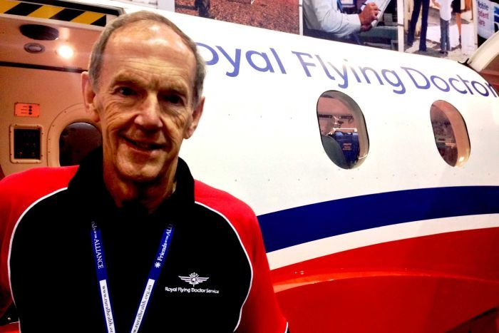 Portrait and close picture of John Setchell standing in front of a RFDS plane.