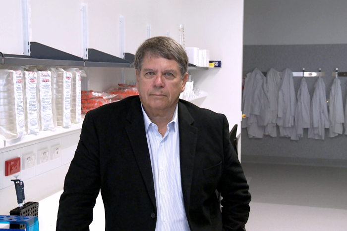 Professor Alan Trounson poses for a photo in a laboratory.