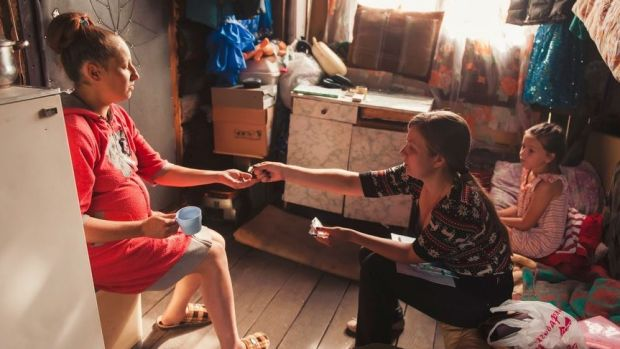HIV+ woman receives antiretroviral therapy pills from PIH Nurse Natalya Shtrevenskaya in her home in Tomsk, Russia.